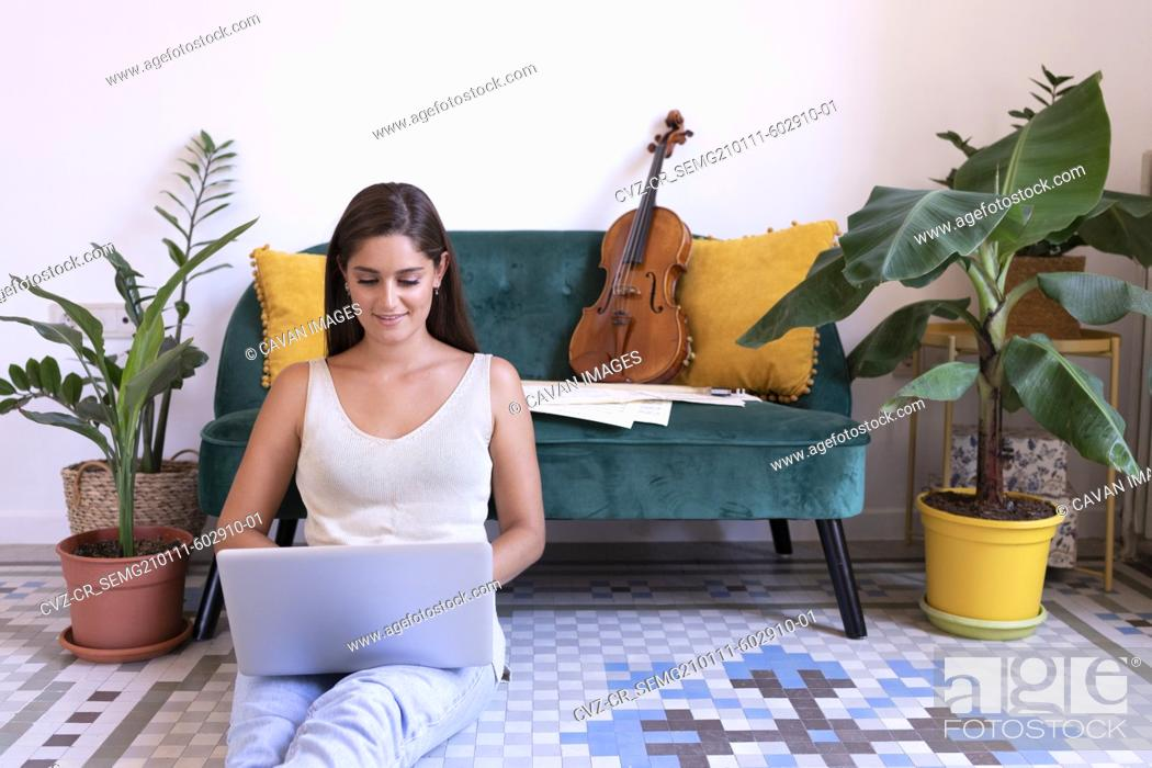 Stock Photo: Young musician girl chatting with her laptop sitting on the floor.
