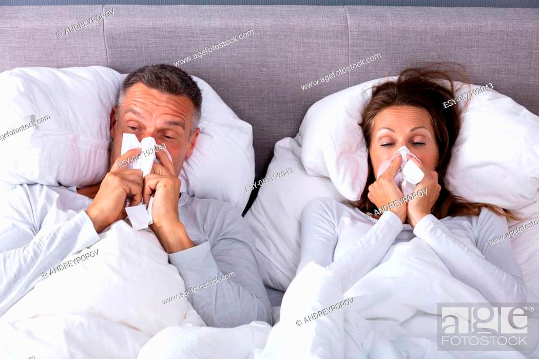 Stock Photo: Close-up Of Mature Couple Lying On Bed Blowing Their Nose In Bedroom.