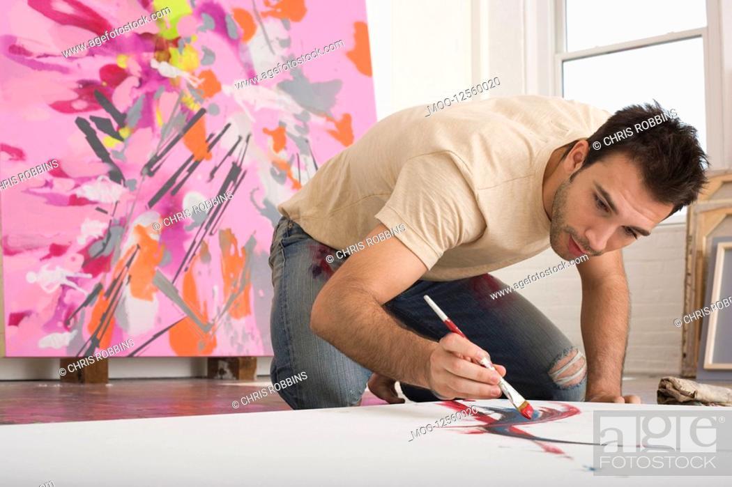 Stock Photo: Artist Working on Canvas on Floor of Studio.