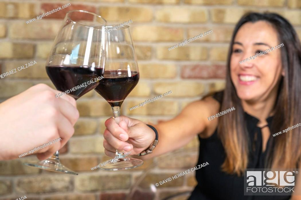 Stock Photo: Close up of young couple toasting with glasses of red wine at restaurant. High quality photo.