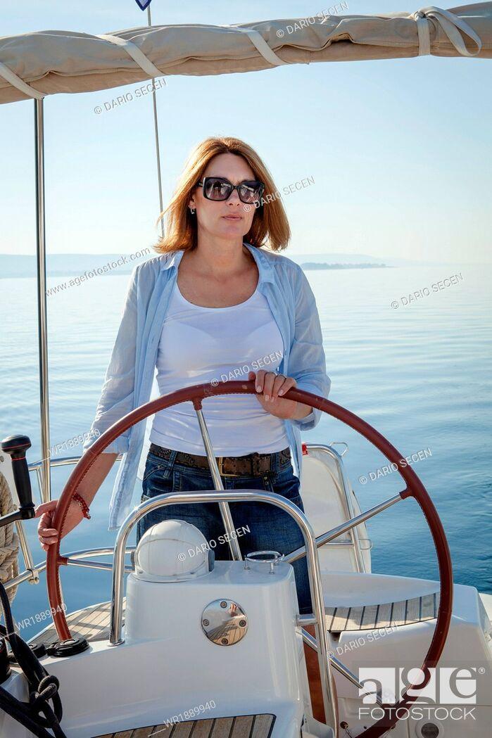 Stock Photo: Mature woman on sailboat, steering, Adriatic Sea, Croatia.