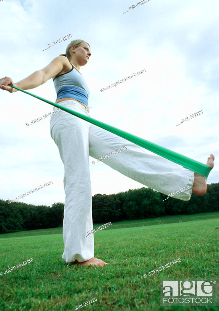Stock Photo: A young woman, 15-20 20-25 25-30 years old, making exercises with an elastic band, making gymnastics.