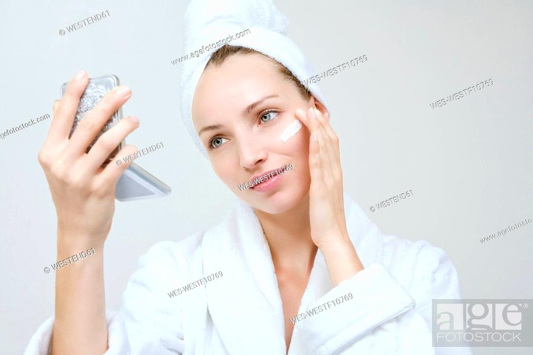 Stock Photo: Young woman applying beauty cream, portrait.