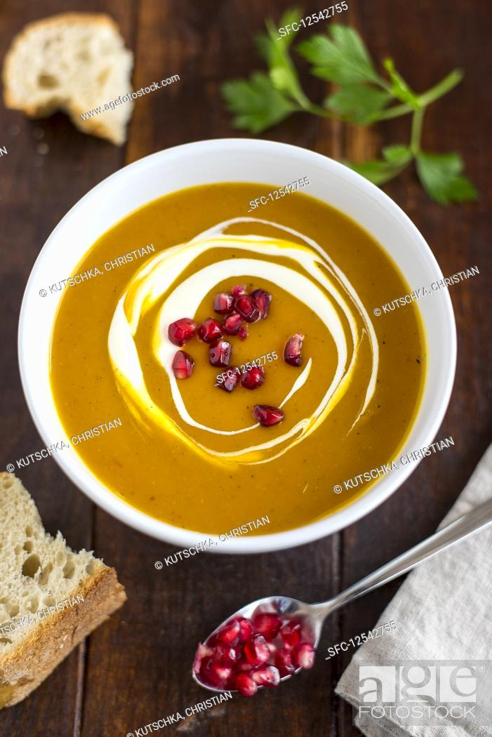 Stock Photo: Cream of pumpkin soup with pomegranate seeds in a white bowl.