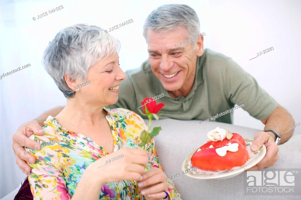 Stock Photo: Senior man romancing woman with valentine cake and red rose.