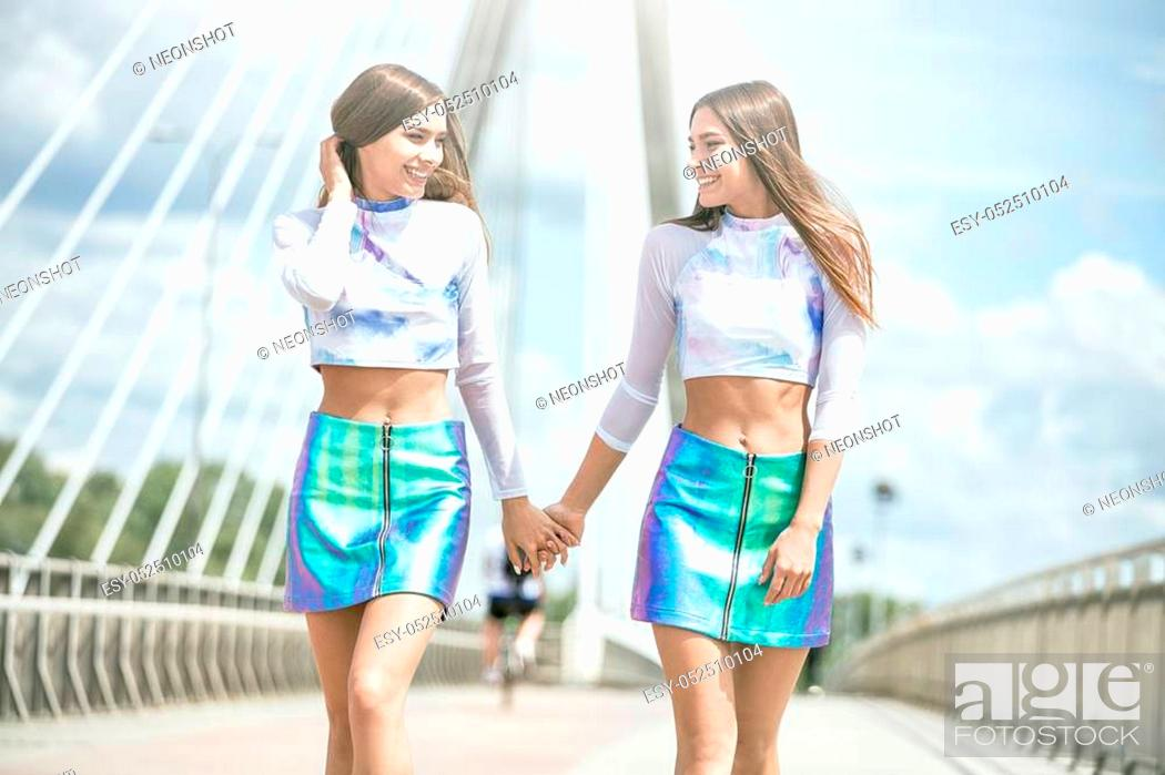 Stock Photo: Twins sisters having fun together. Caucasian beautiful girls wearing fashionable clothes, smiling.