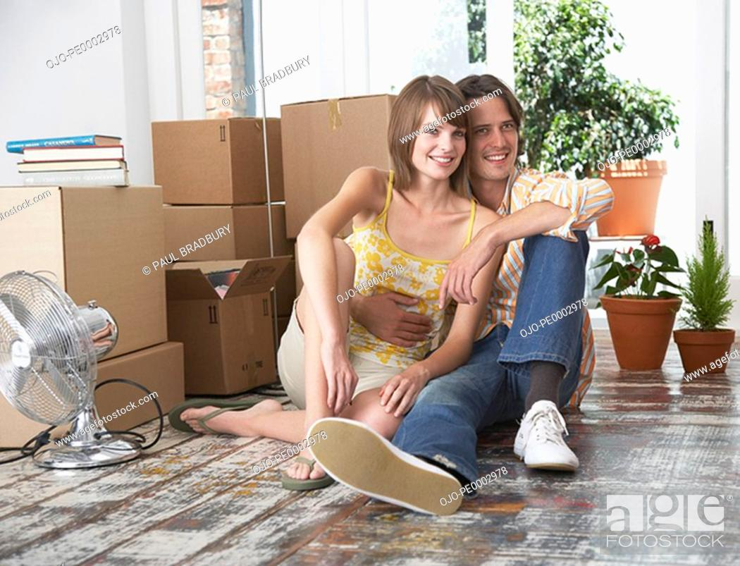 Stock Photo: Man and woman sitting on hardwood floor with cardboard boxes and potted plants with fan.