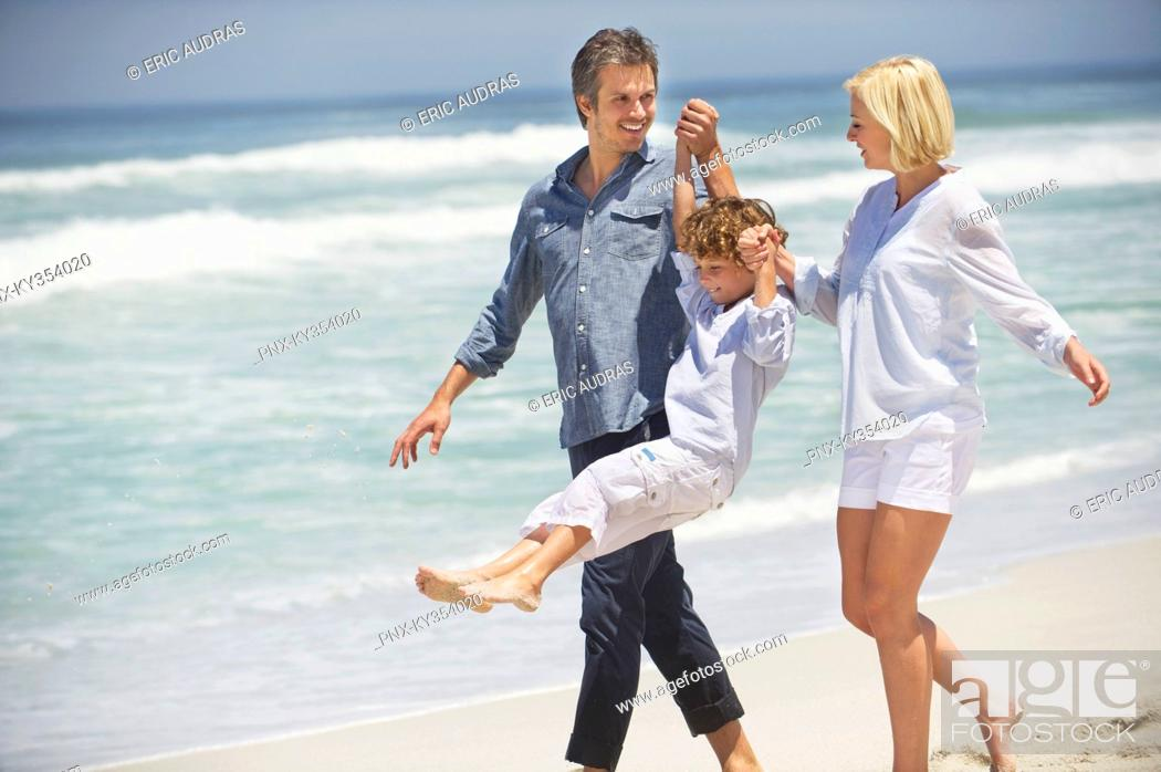 Stock Photo: Couple walking with their son on the beach.