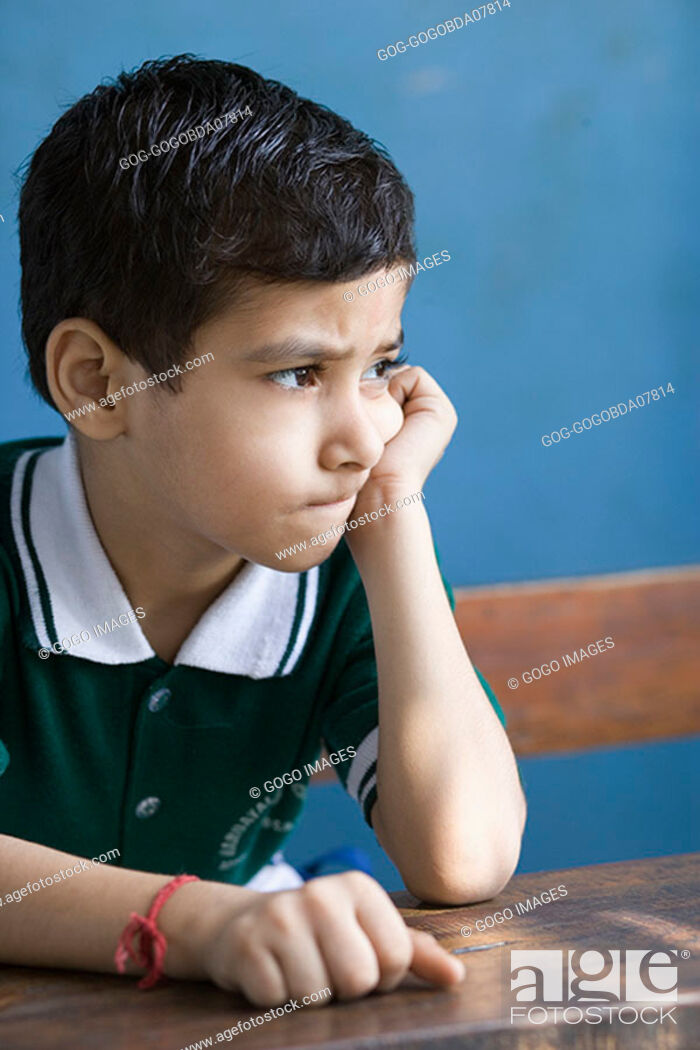 Stock Photo: Young boy leaning on desk.
