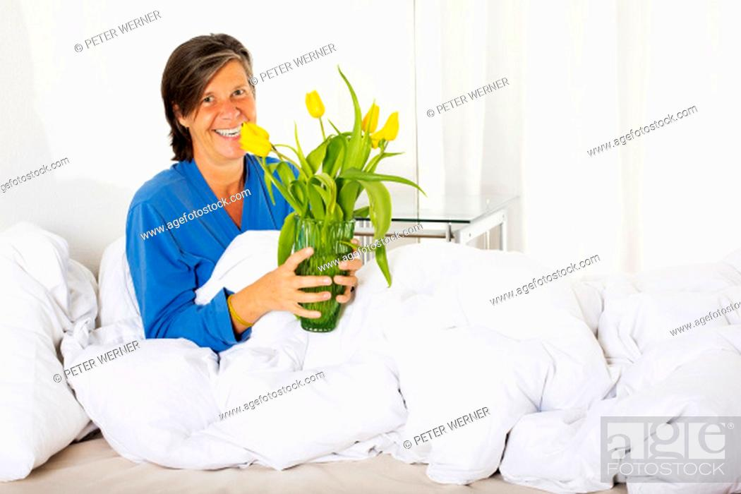 Stock Photo: woman in her fifties sitting in bed and holding a vase with flowers.
