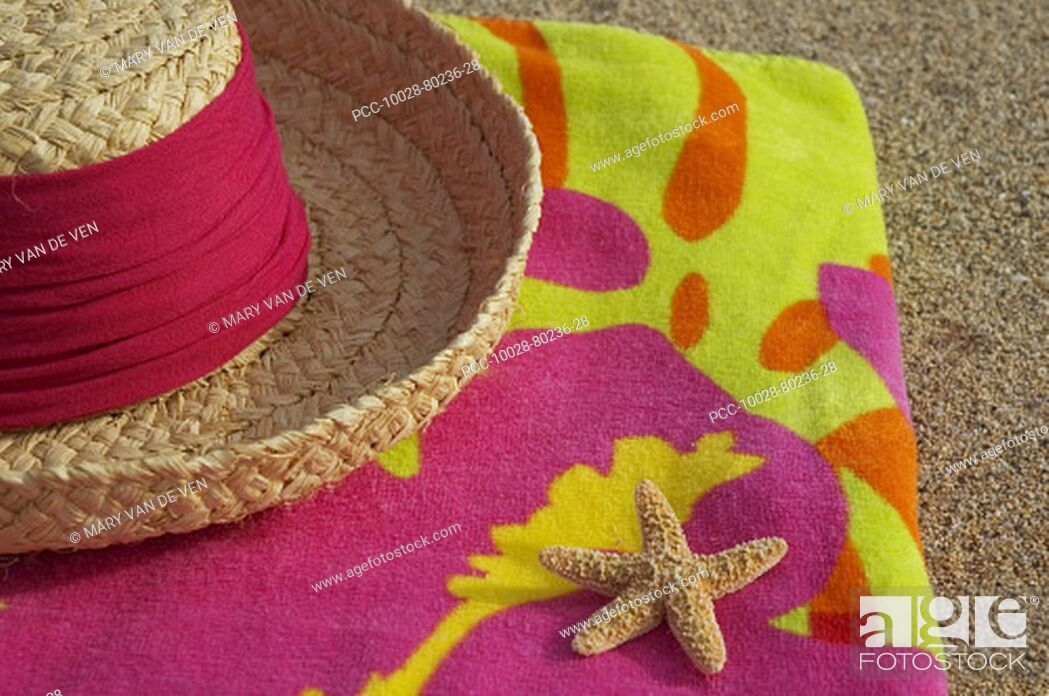 Stock Photo: Straw hat and seastar on multi-colored towel, on sandy beach.