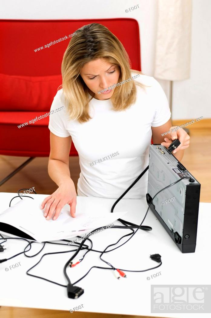 Stock Photo: Woman trying to connect DVD player.