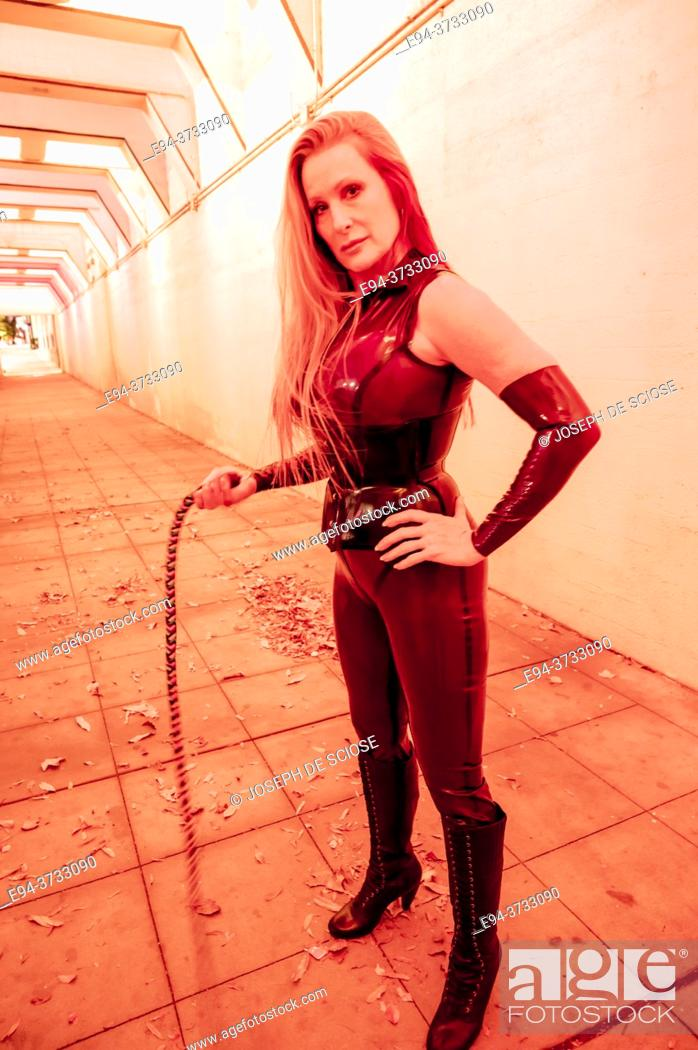 Imagen: A beautiful 51 year old tall blond dominatrix woman dressed a latex costume, holding a whip in a lighted underpass.