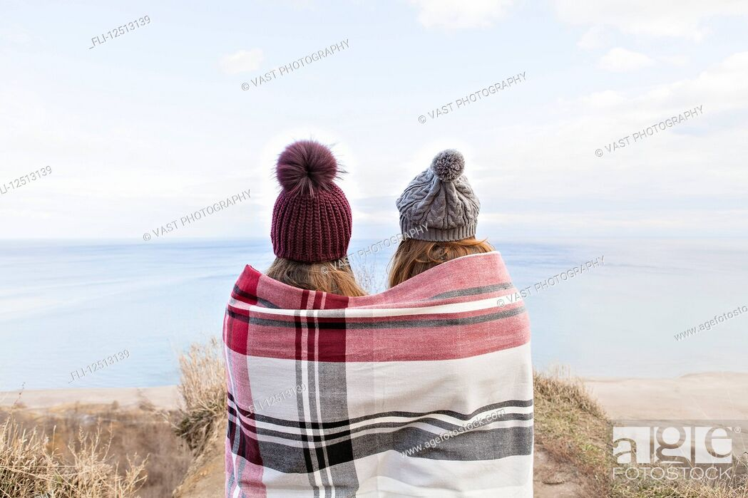 Stock Photo: Two friends wrapped in a blanket standing on bluffs looking out over Lake Ontario; Scarborough, Ontario, Canada.