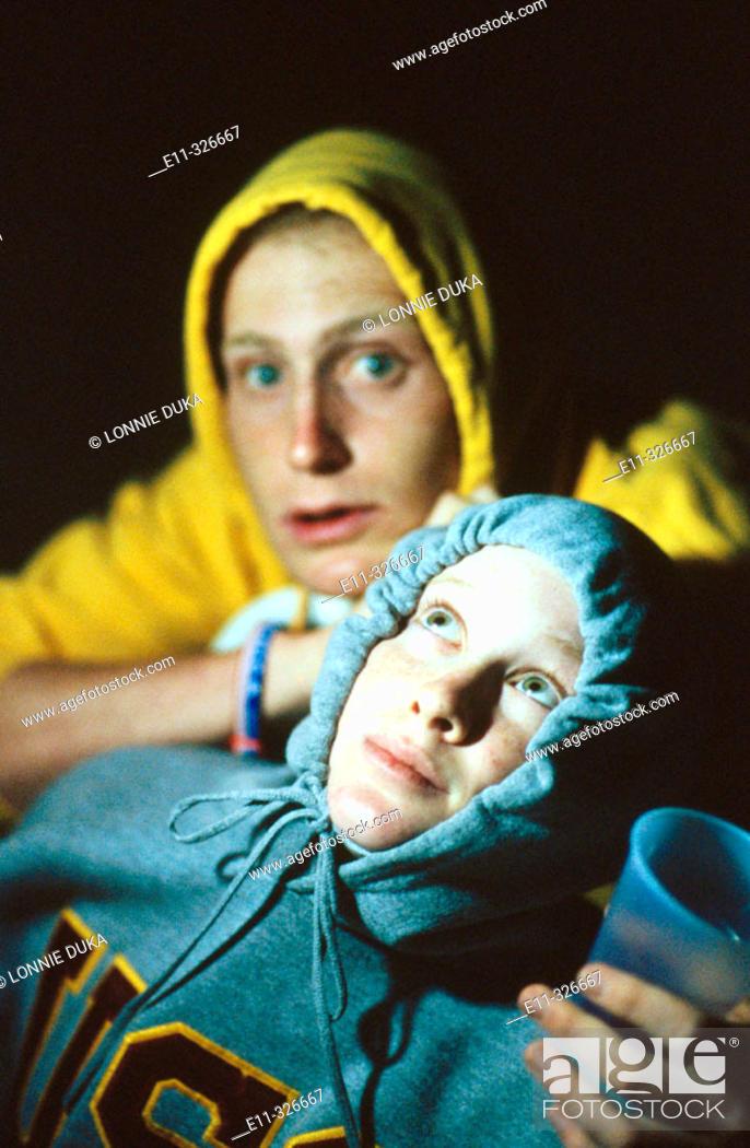 Stock Photo: Young couple wearing hooded sweatshirts, outdoors/night.