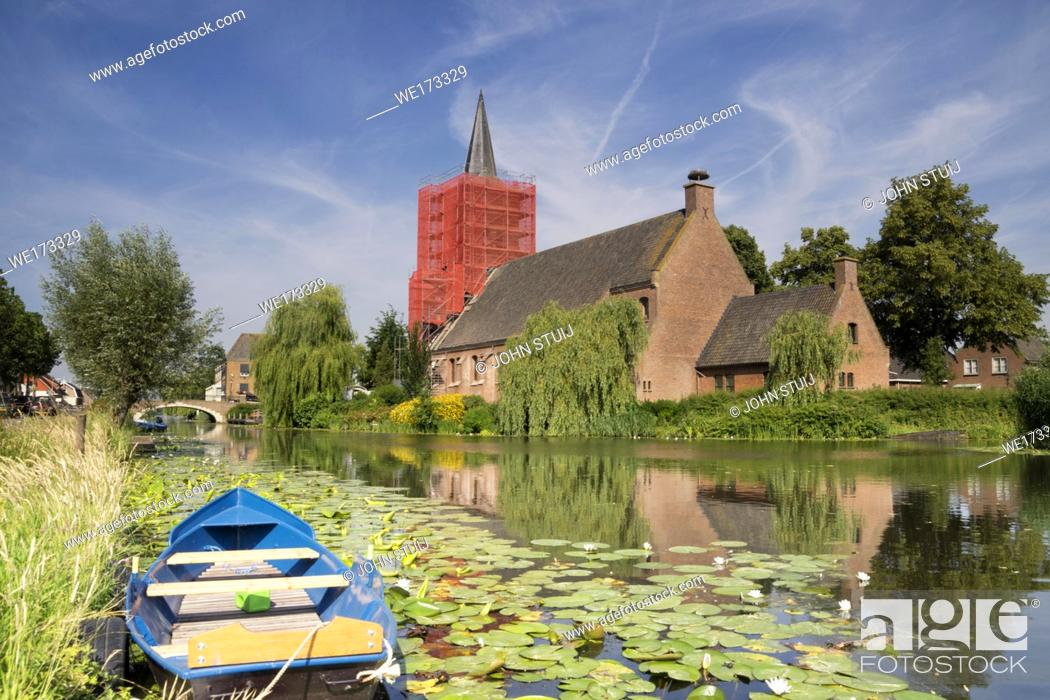 Stock Photo: Restauration works on the church tower in Bleskensgraaf on the small river Graafstroom in the Dutch province South-Holland.