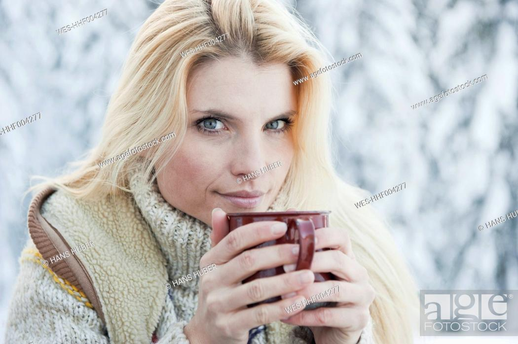 Stock Photo: Austria, Salzburg County, Mid adult woman drinking tea, smiling.