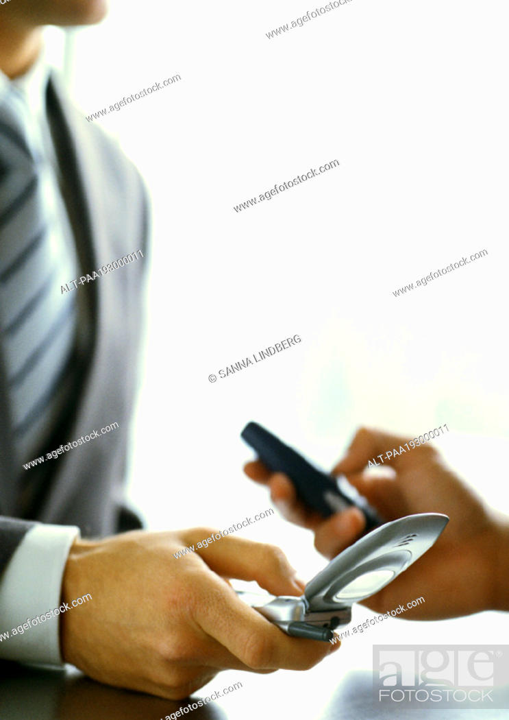Stock Photo: Business people's hands, exchanging numbers with cell phones, close-up.