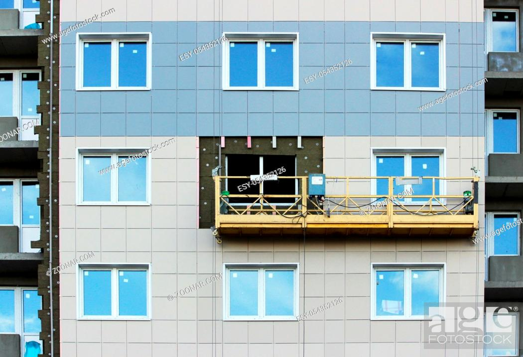 Stock Photo: construction suspended yellow cradle without workers on a newly built high-rise building.