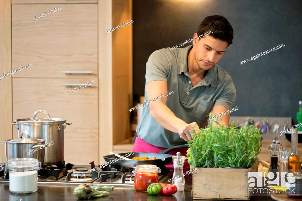 Stock Photo: Man preparing food in the kitchen.