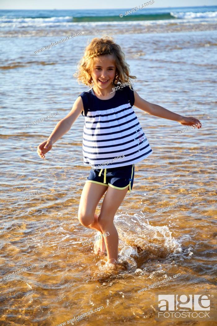 Stock Photo: Girl playing on the beach, Zarautz, Gipuzkoa, Basque Country, Spain, Europe.