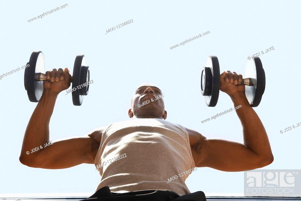 Stock Photo: Man Lifting dumbbells low angle view close up.