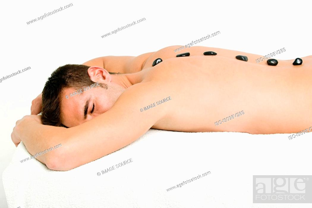 Stock Photo: Young man having hot stone therapy.