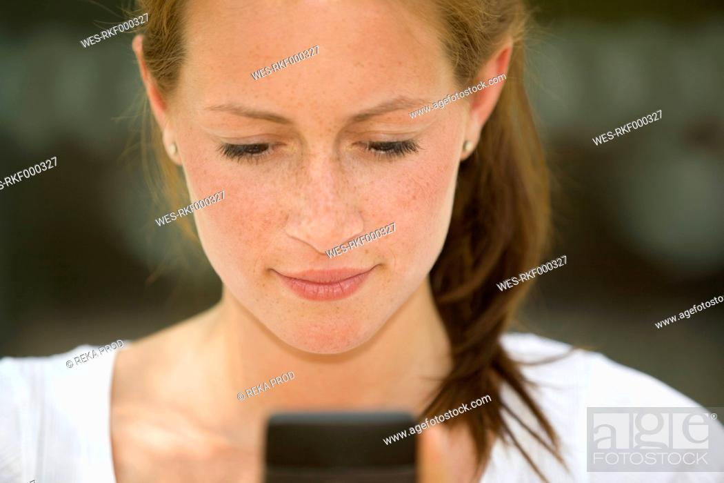 Stock Photo: Germany, North Rhine Westphalia, Cologne, Young woman using smart phone, smiling.