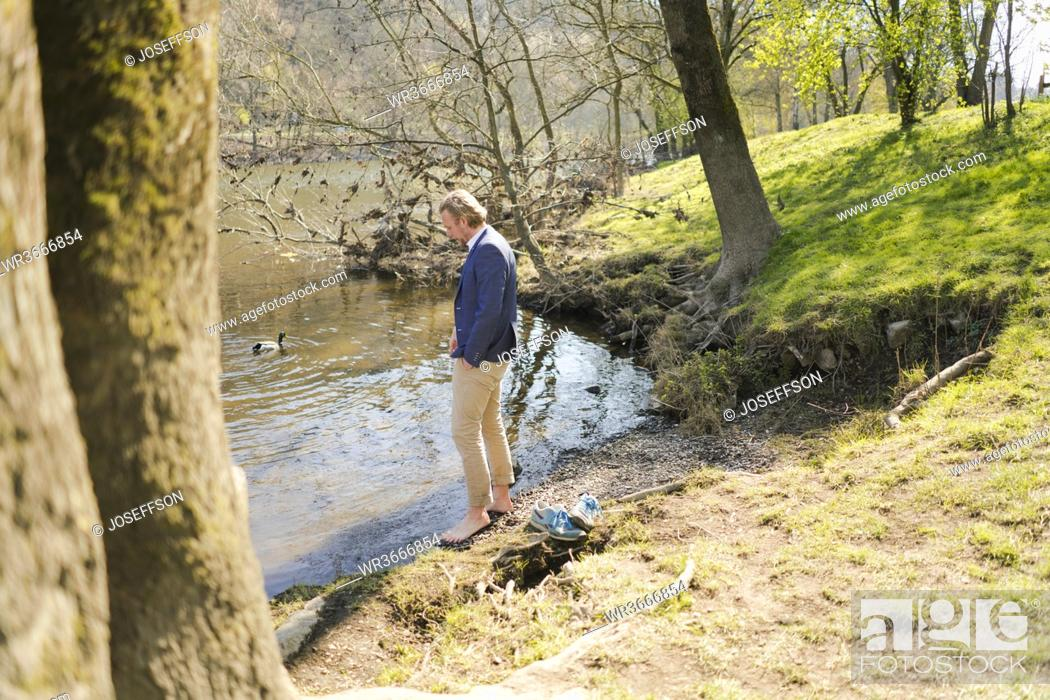 Stock Photo: Male entrepreneur standing at riverbank in park on sunny day.