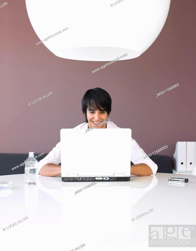 Stock Photo: Man Using Laptop at White Table.