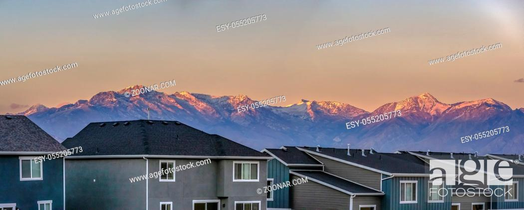Stock Photo: Panorama of homes in front of Timpanogos sunset. Copy space in the sky with pink colors on the tips of Timpanogos mountains with some snow on the very peaks of.