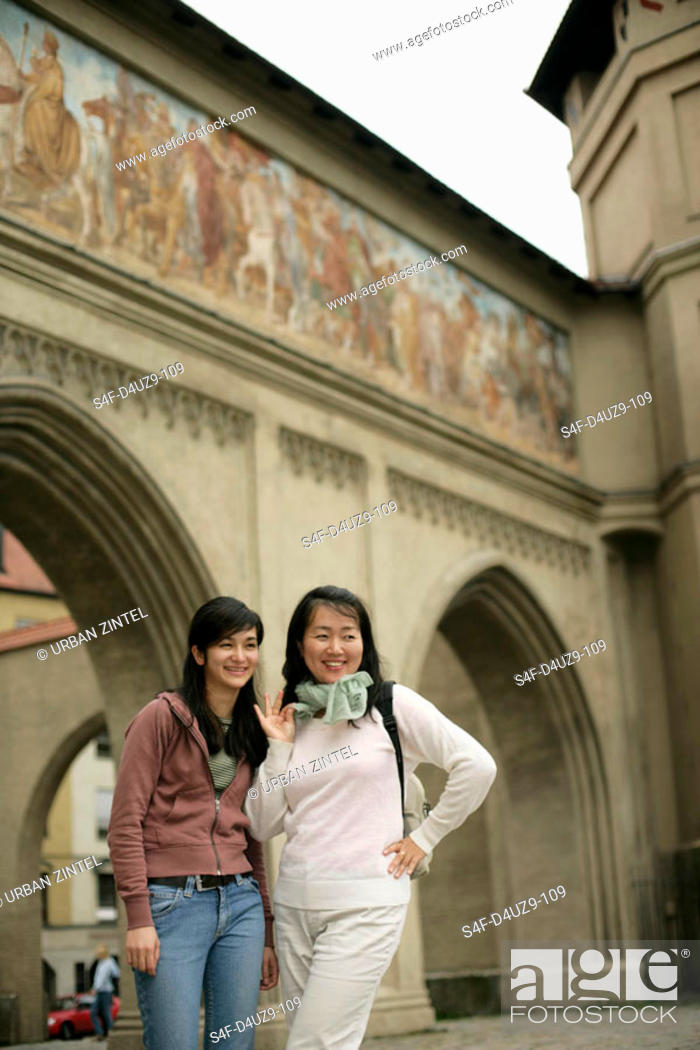 Stock Photo: Two young Asian women standing in front of a painted gate, selective focus.