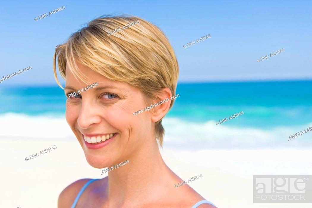 Stock Photo: Portrait of a woman smiling on the beach.