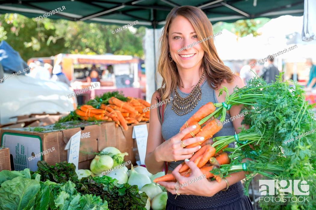 Stock Photo: Woman at fruit and vegetable stall holding carrots.