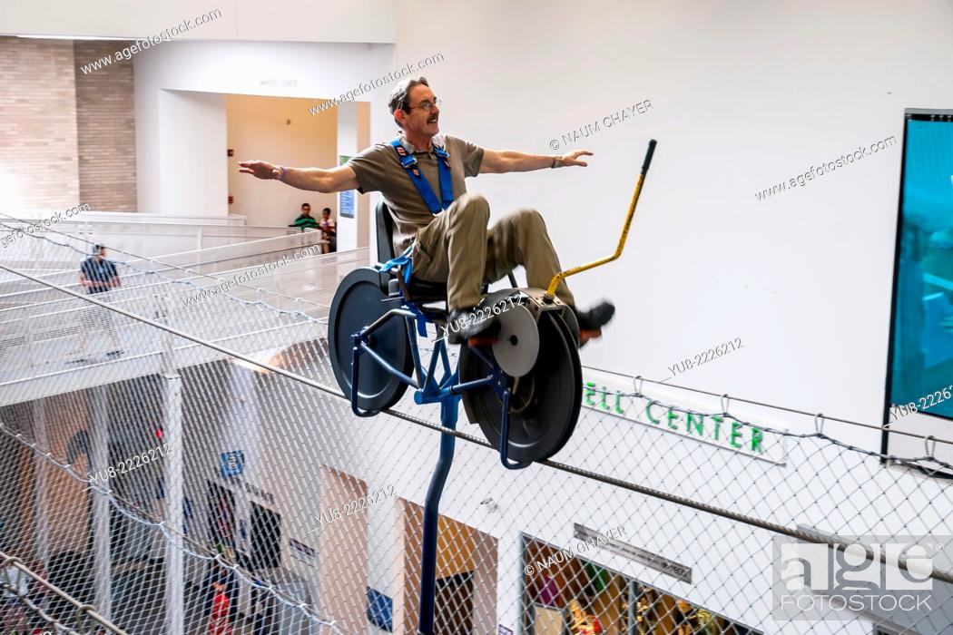 Stock Photo: A man rides on a tightrope on sky bike, The Franklin Institute, Philadelphia, Pennsylvania, PA, USA, North America.