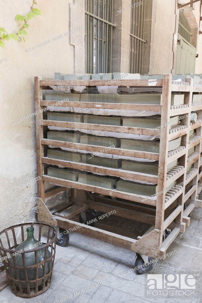 Imagen: Mellow green blocks of olive Marseille soap on traditional wooden racks drying in the sun outside the Marius Fabre soap factory, Salon, Provence, France.