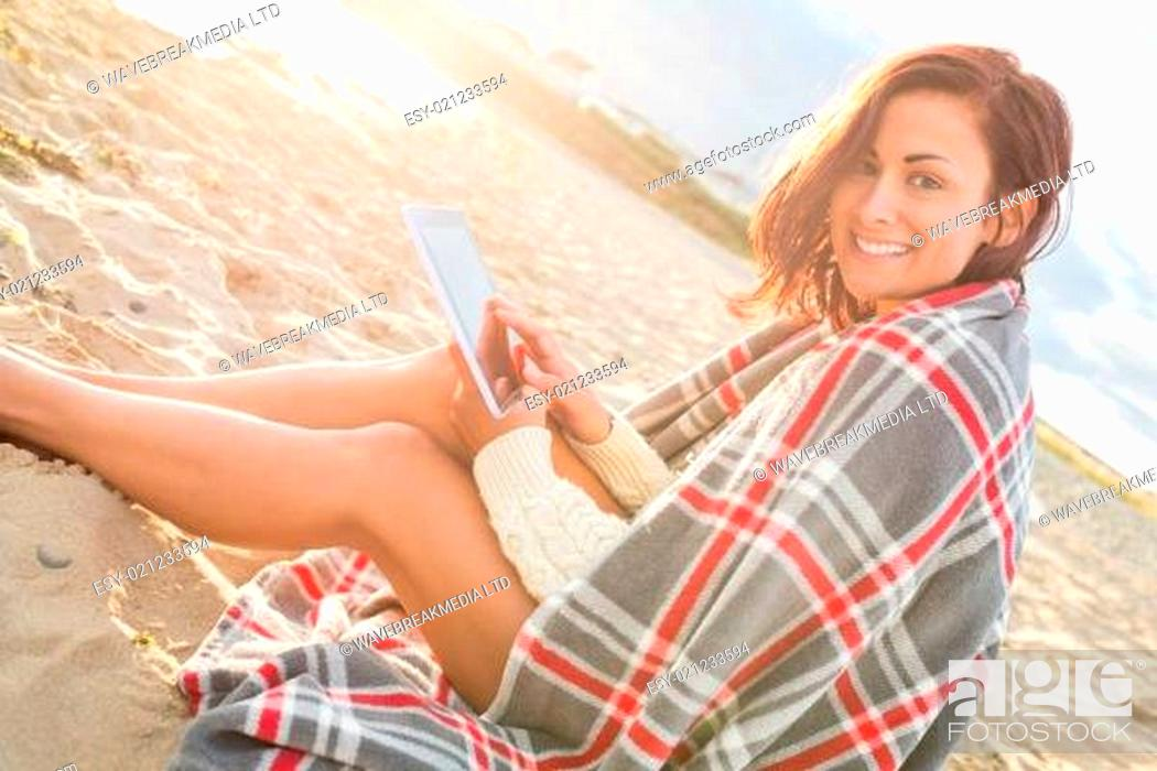 Stock Photo: Woman covered with blanket using tablet PC at beach.