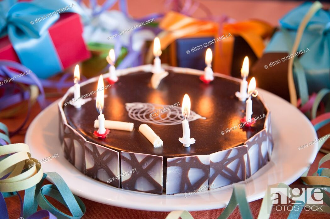 Stock Photo: big chocolate cake with birthday candles burning between gift boxes.