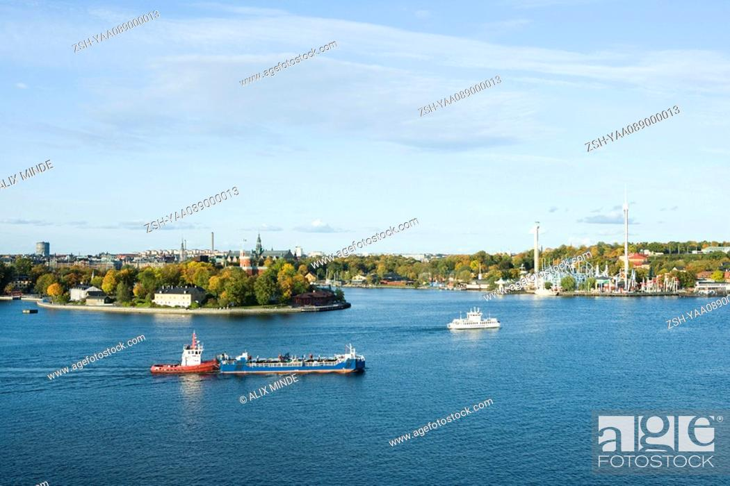 Stock Photo: Sweden, Stockholm, Lake Malaren, tugboat pushing barge, city in background.