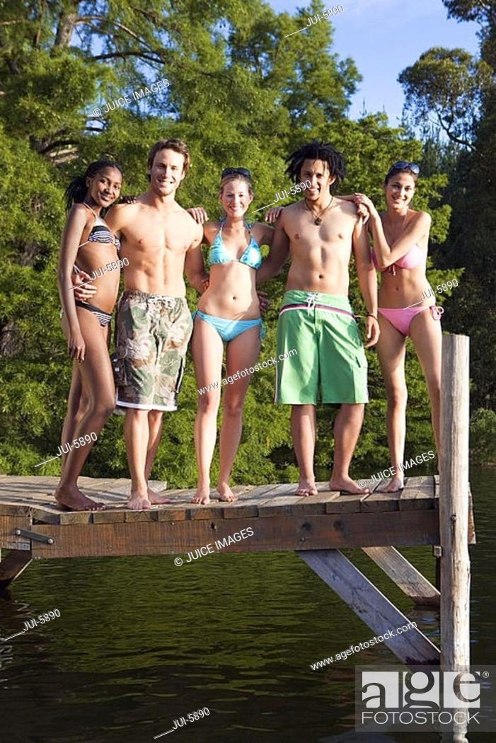 Stock Photo: Five young adults, in swimwear, standing side by side on lake jetty, smiling, front view, portrait.