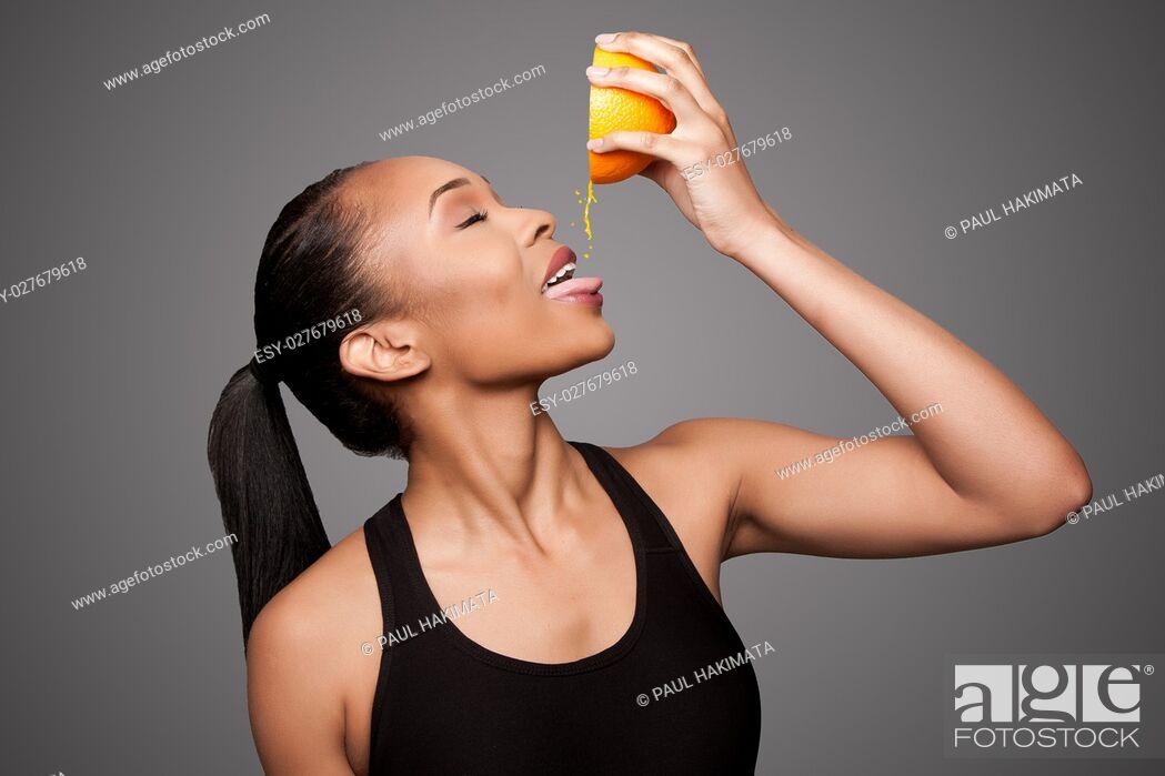 Stock Photo: Beautiful healthy happy black asian woman squeezing delicious orange juice mandarin fruit.