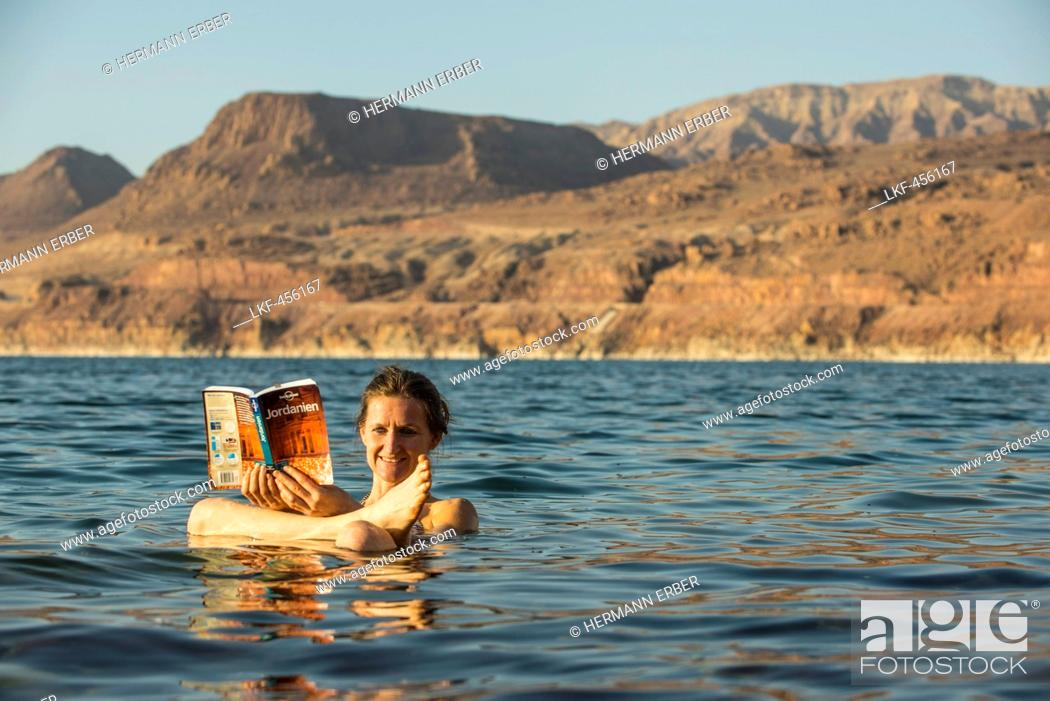 Stock Photo: Woman reading a guidebook in Dead Sea, Jordan, Middle East.