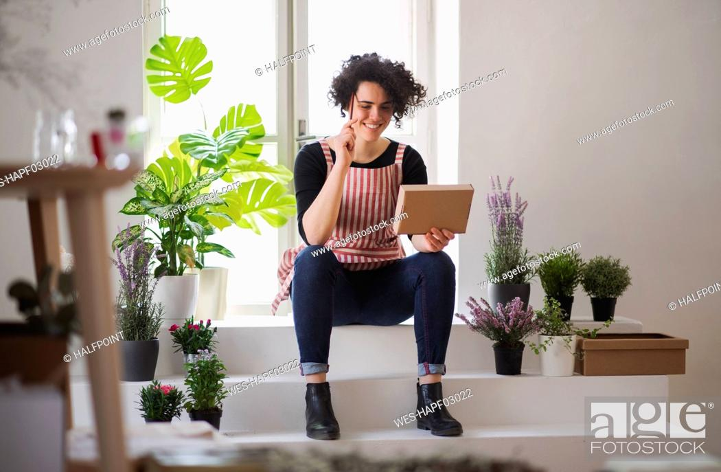 Stock Photo: Smiling young woman with cardboard box in a small shop with plants.