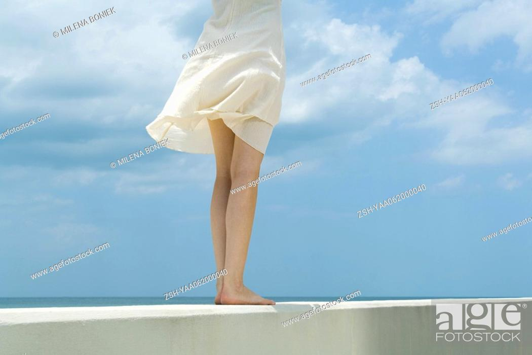 Stock Photo: Woman standing on low wall, tousled by breeze, cropped rear view.