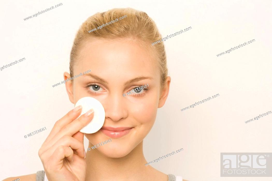Stock Photo: Young woman using cotton pad on face, portrait.
