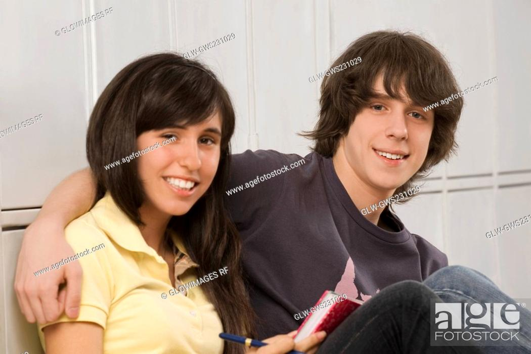 Stock Photo: Portrait of a teenage boy arm around with a teenage girl and smiling.