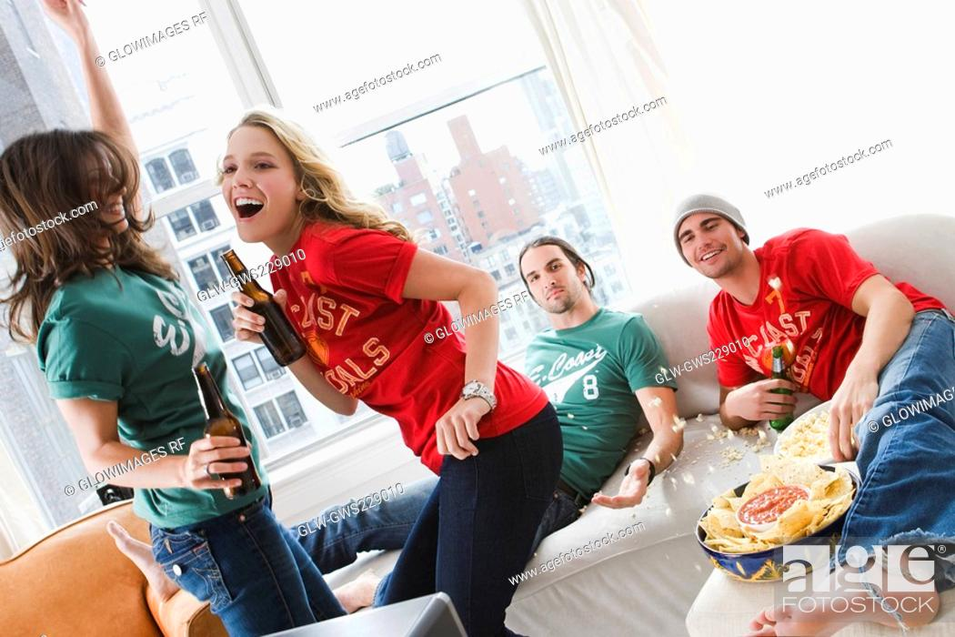 Stock Photo: Two young men lying on a couch and two young women drinking beer and dancing.