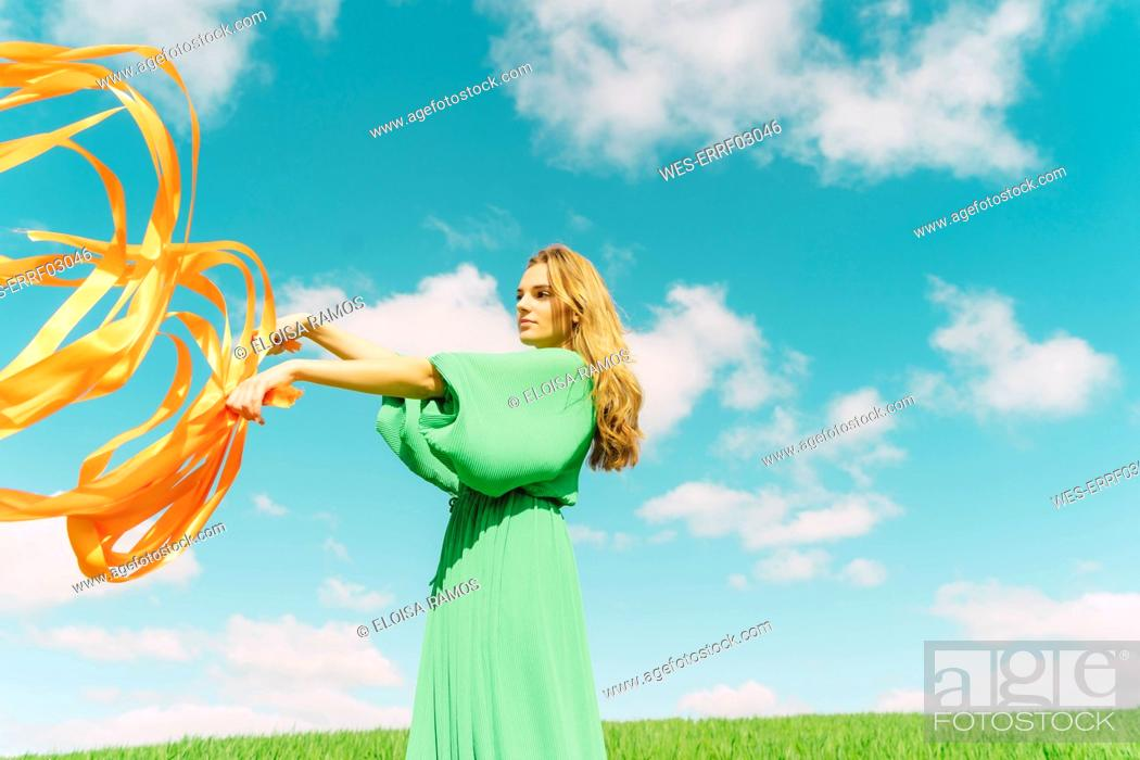 Stock Photo: Young woman wearing a green dress standing in a field with blowing ribbons.