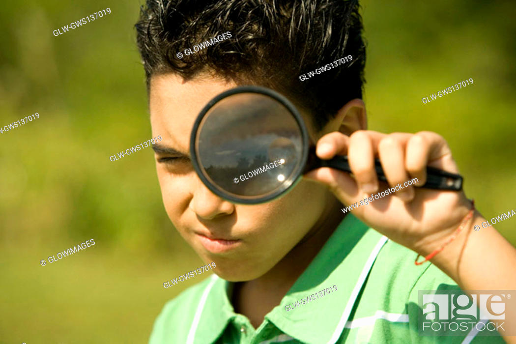 Stock Photo: Portrait of a boy looking through a magnifying glass.