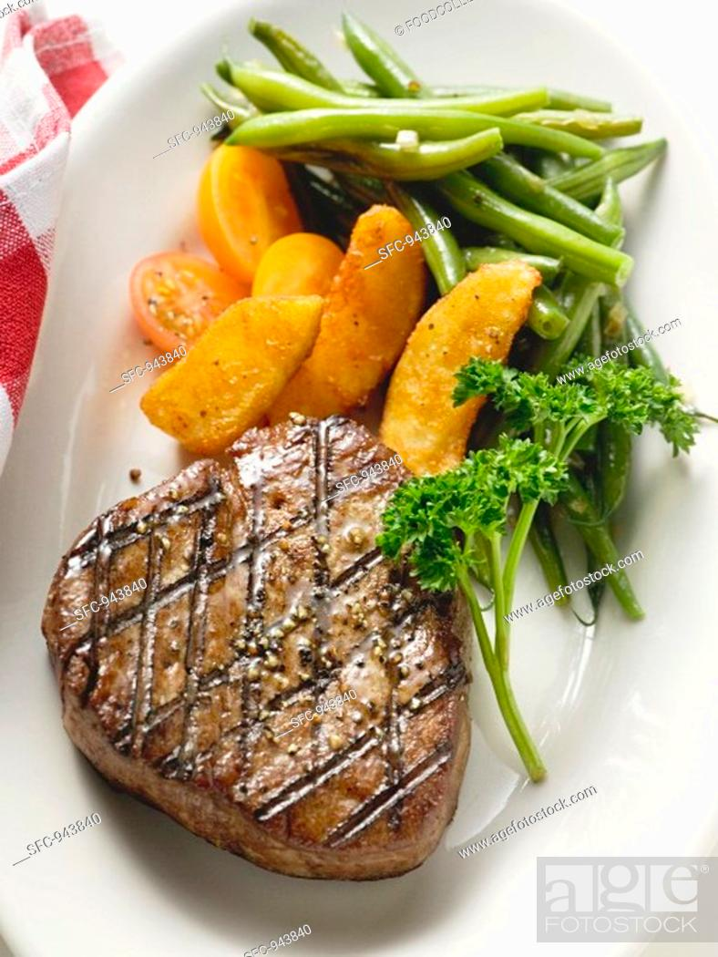 Stock Photo: Grilled fillet steak with country potatoes and bean salad.